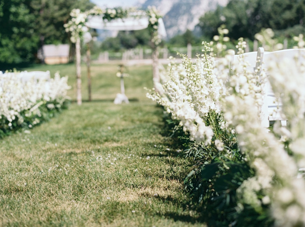 La Caille Utah Summer Wedding, flowers lining a ceremony aisle, ceremony aisle flowers, white delphinium lining a ceremony aisle, ceremony aisle treatment, flowers lining the ceremony aisle, la caille utah, stunning ceremony aisle flowers, jacque lynn photography, Wedding Flower Utah Calie Rose